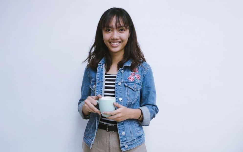 mujer riendo con una taza en la mano