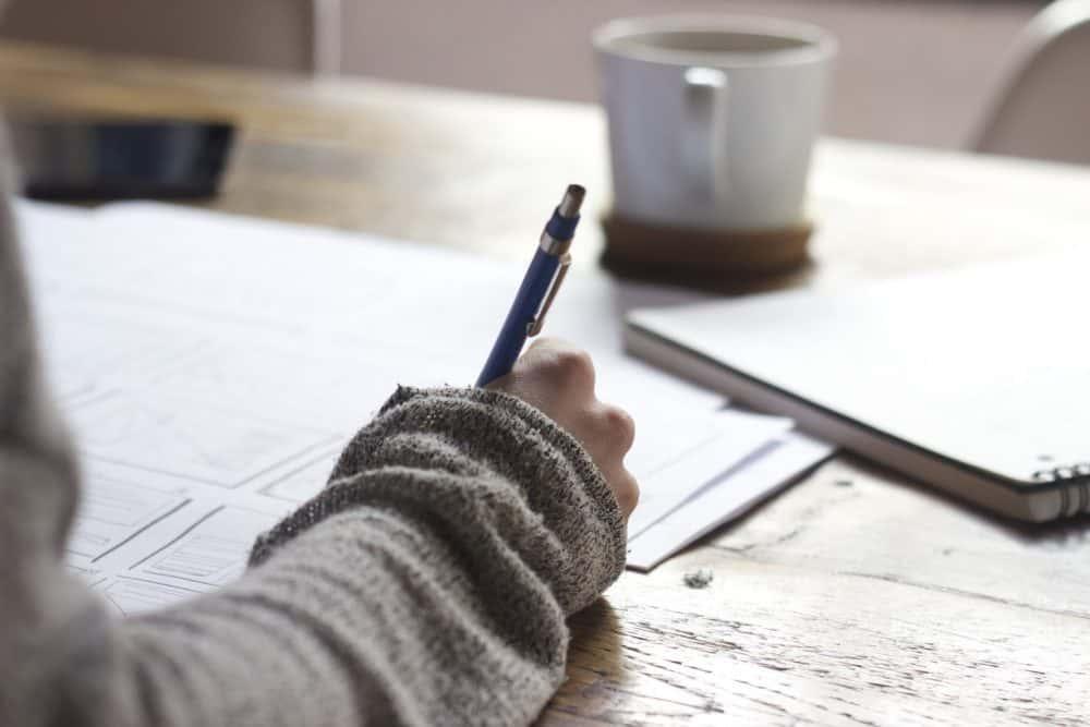 mujer escribiendo con un bolígrafo